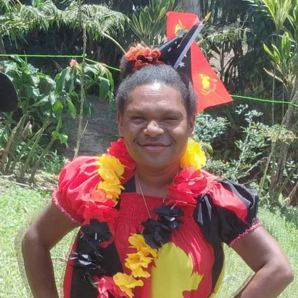 A young woman smilies with Papua New Guinea flags in the background