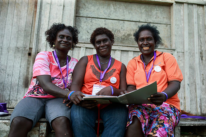 Women attending the Women Human Rights Defenders Forum sit smiling in Bougainville.