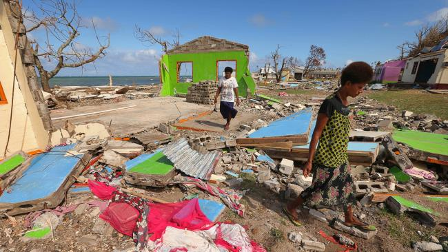 Women walk among the destroyed homes in the wake of Cyclone Winston in Fiji. Photo: Lyndon Mechielsen/The Australian
