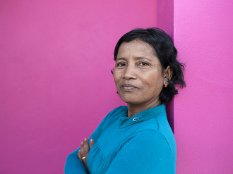 A woman stands with her arms crossed, she is looking into the camera