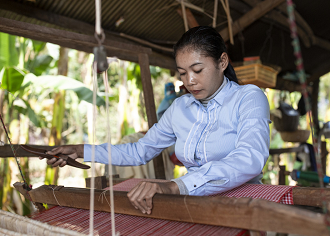 A woman is working on a weaving loom