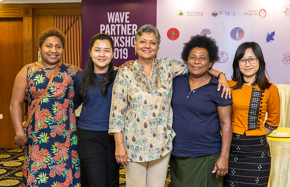 Group of women stand with Srilatha Batliwala at the WAVE Partner Workshop