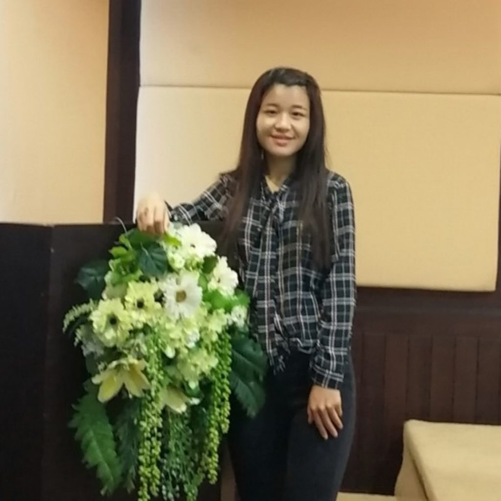 A young woman stands with a wreath of flowers