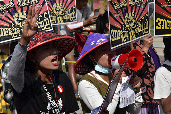 Women speak into a megaphone at a rally in Myanmar