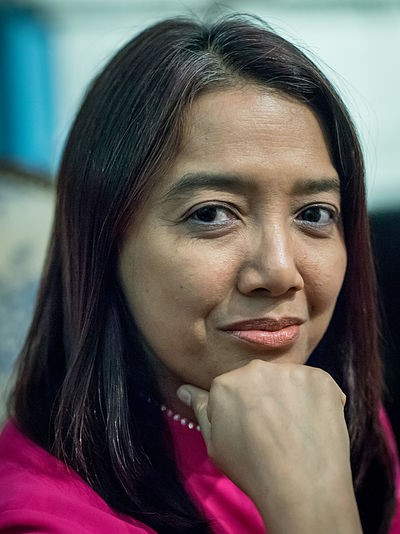 A photo of Myanmar activist Thin Thin Aung. It is a close up portrait of her. Her head is gently resting on her closed fist and as she looks into the camera with a closed-mouth smile.