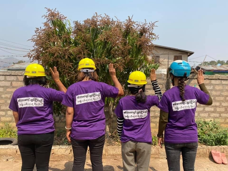 A photo of four women with their backs to the camera. They are wearing matching purple shirts with words in Burmese written across the back. Each woman is wearing a hard hat and holding up their right hand with three fingers lifted in a sign of resistance.
