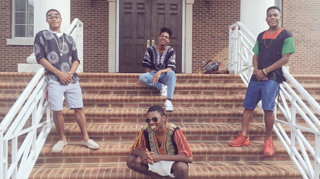 Four men wearing Dashikis in front of a University building. Photo: Complex