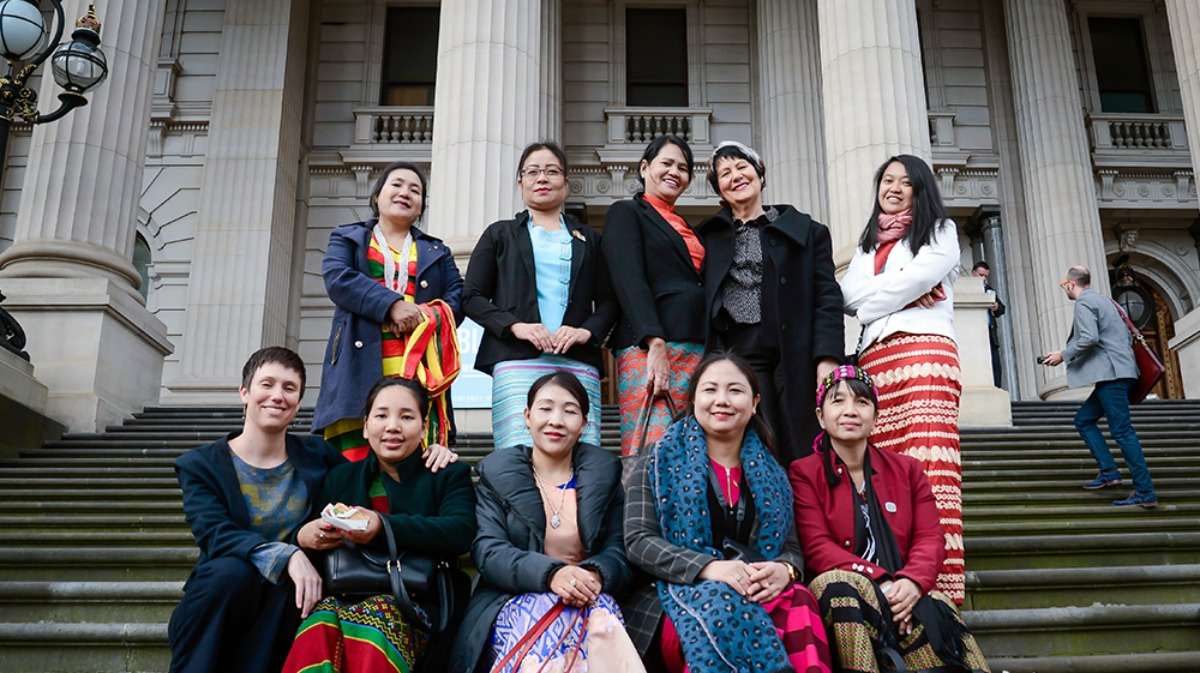Image of women Myanmar MPs, IWDA staff and Emilys List founder standing outside Victoria's parliament building