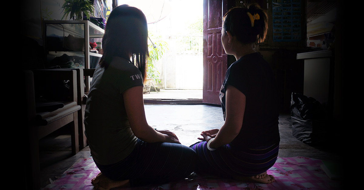 Image of two women in Myanmar sitting on a mat, looking into the distance.