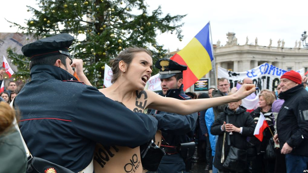 Police restrain a FEMEN activist outside The Vatican. Photo: AFP