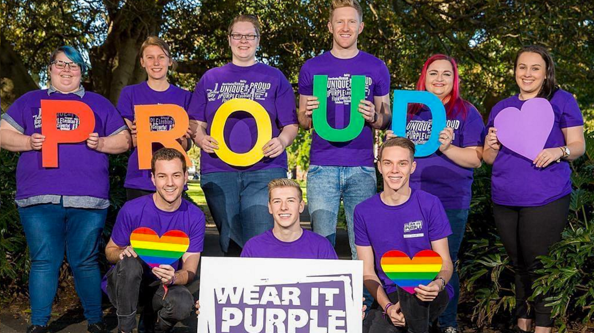 "Image of young people wearing purple and a sign reading: ""proud"""