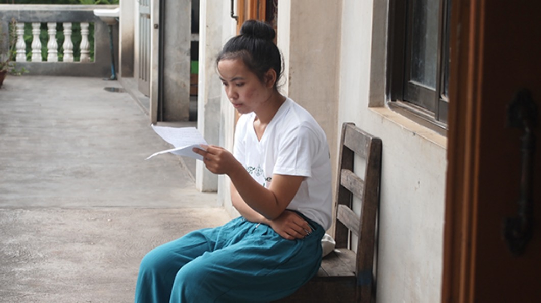 Image of a woman sitting in a hallway, reading a piece of paper.