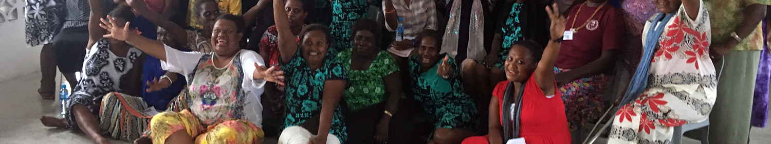Image of woman sitting in a group in Solomon Islands, looking at the camera.