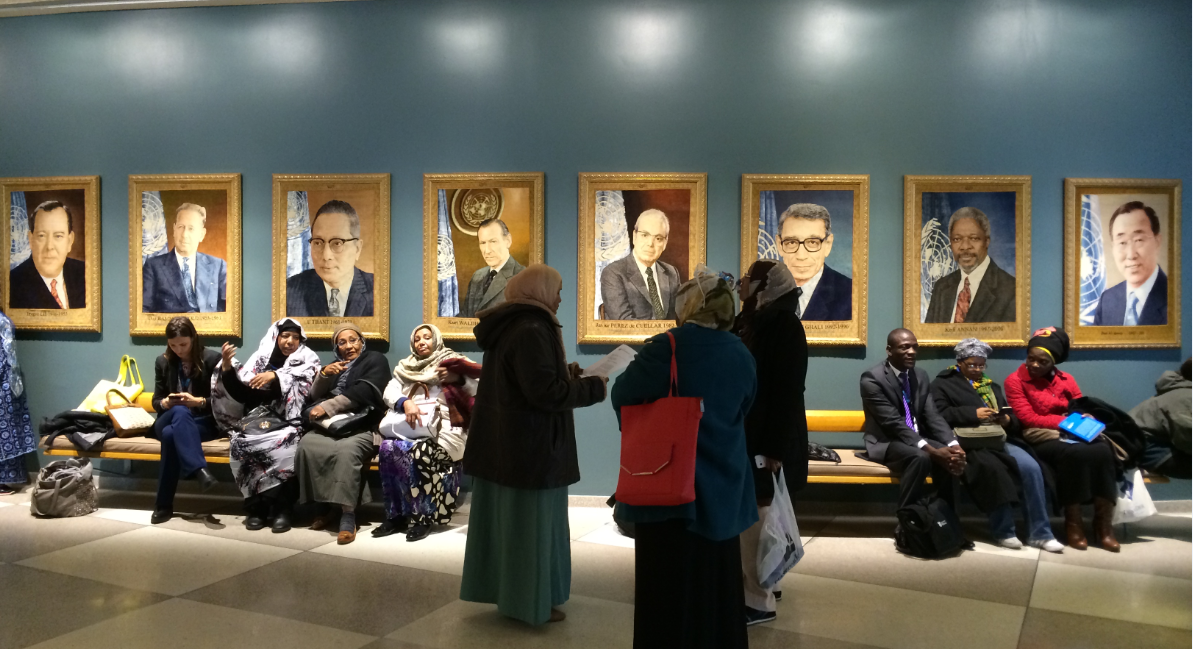Women gather in front of portraits of the previous eight UN Secretary Generals at the 59th Commission on the Status of Women in 2015. Photo: Joanna Hayter